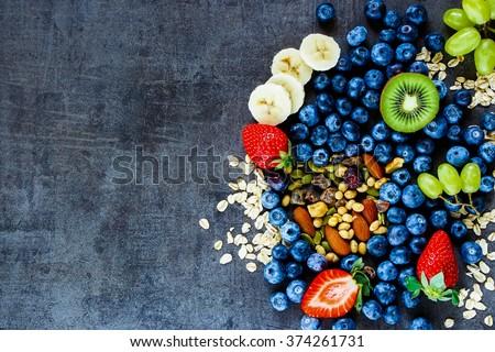 Fresh healthy ingredients (oat flakes, banana, berries with yogurt and seeds) for breakfast or smoothie on dark vintage background - Healthy food, Diet, Detox, Clean Eating or Vegetarian concept. - stock photo