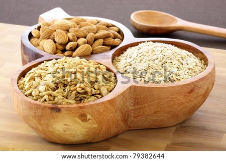 fresh healthy rolled oats, muesli and almonds on wooden rustic serving utensil. part of a healthy and delicious breakfast - stock photo