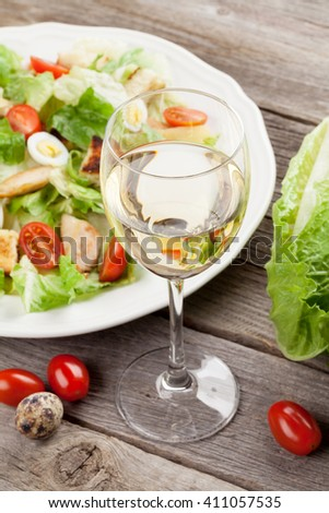 Fresh healthy salad and white wine on wooden table - stock photo