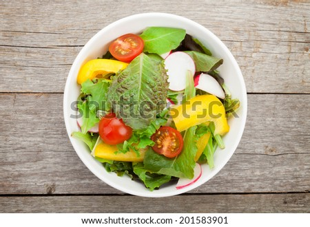 Fresh healthy salad on wooden table. View from above - stock photo