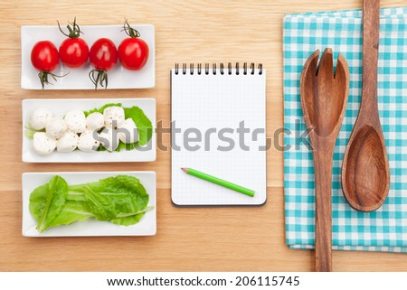 Fresh healthy salad, tomatoes, mozzarella and notepad for copy space on wooden table - stock photo