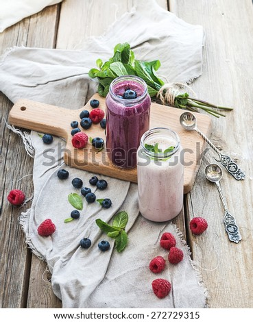 Fresh healthy smoothie with blueberries, raspberries in glass jars and mint over rustic wood background - stock photo