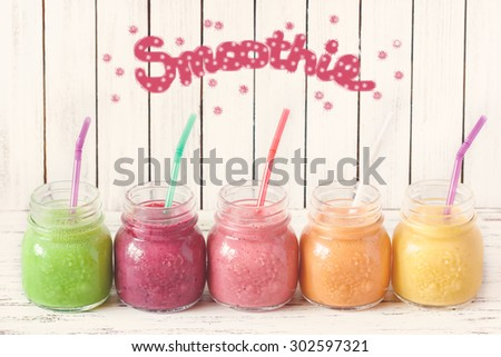 Fresh healthy smoothies with straws on a kitchen board. Toned photo. - stock photo
