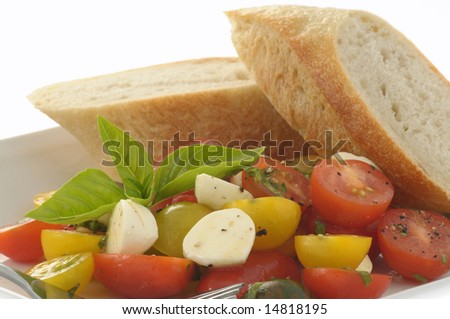 Fresh heirloom toatoes with fresh herbs and bread. - stock photo