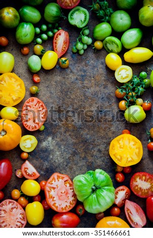 Fresh heirloom tomatoes background, organic produce at a Farmer's market. Tomatoes frame. - stock photo