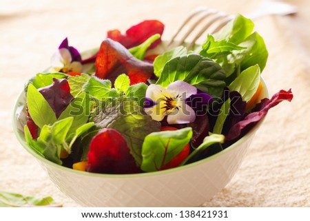 Fresh herb salad with leafy greens and nasturtium flowers served in a white ceramic bowl - stock photo