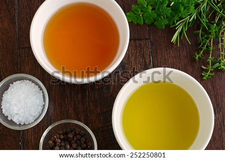 Fresh herbs, agave syrup, olive oil ,dijon mustard and rice wine vinegar with sea salt and peppercorns are the ingredients for a fresh healthy salad dressing - stock photo