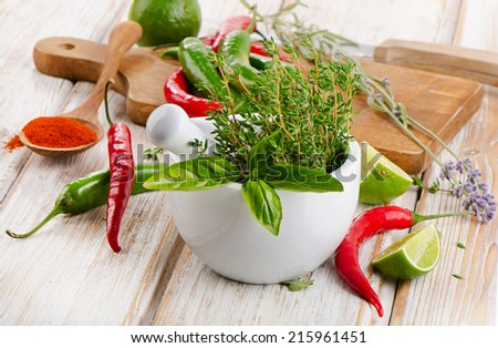 Fresh herbs and red chili peppers on wooden table. Selective focus