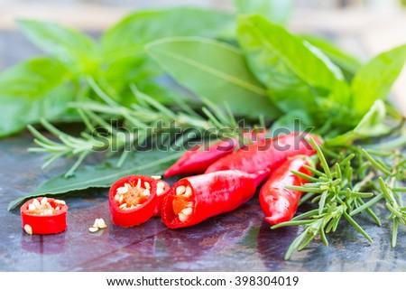 Fresh herbs and seasoning (red chili, rosemary, basil, bay leaf), olives on black stone background - stock photo