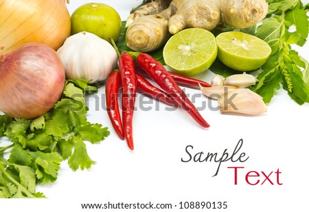 Fresh herbs and spices (chili, garlic, ginger, lemon, onion, shallot, kaffir lime leaves, coriander and hot basil leaves) - stock photo