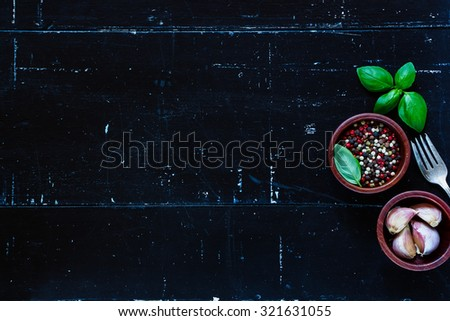 Fresh herbs and spices (pepper, garlic and basil leaves) on dark vintage background with space for text. Vegetarian food, health or cooking concept. - stock photo