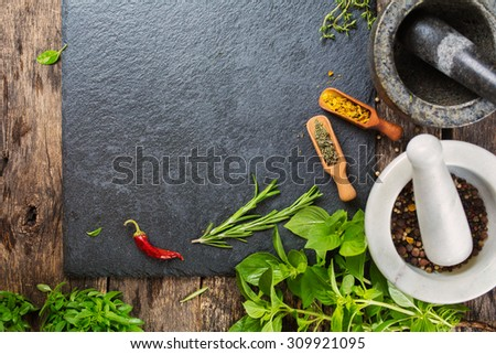 Fresh herbs and spices. Slate background with copyspace.  - stock photo