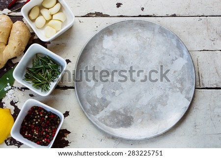 Fresh herbs and spices with old metal plate on white rustic background. - stock photo