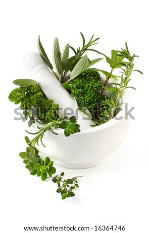Fresh herbs in a white mortar with pestle.  Herbs include rosemary, sage, mint, parsley, oregano and thyme.