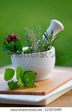 Fresh herbs in the mortar - alternative medicine - stock photo
