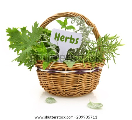 Fresh herbs in wicker basket with a tag - stock photo