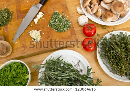 Fresh Herbs, mushrooms, tomatoes, garlic and unions on plates and cutting board on a rustic wooden kitchen counter, with a kitchen knife - stock photo