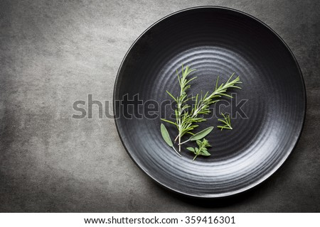 Fresh herbs on black plate over gray slate.  Aerial view with copy space.