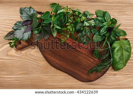 Fresh herbs on wooden cutboard on wooden table. Top view, flat lay