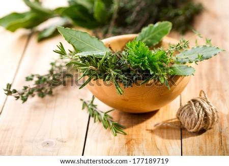 fresh herbs on wooden table - stock photo