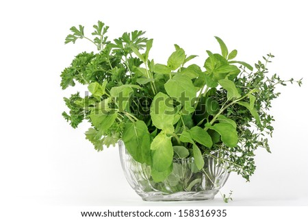 Fresh herbs, thyme, mint and parsley placed in a glass utensil - stock photo