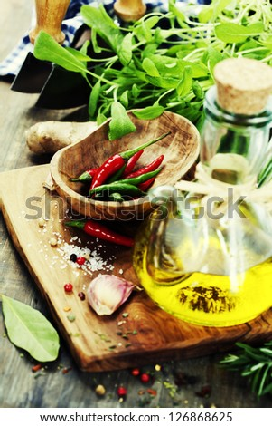 fresh  herbs  with  mezzaluna, olive oil and vegetables on cutting board - stock photo
