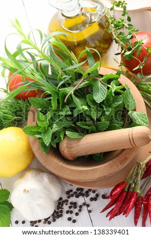 fresh herbs with mortar and pestle - stock photo