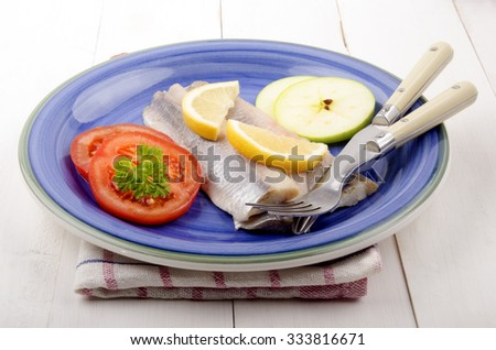 fresh herring with lemon slice, apple, tomato and parsley on a plate - stock photo