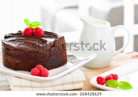 Fresh home made sticky chocolate cake with raspberries and a jug of fresh pouring cream - stock photo