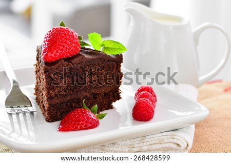 Fresh home made sticky chocolate cake with strawberries and raspberries with a jug of fresh pouring cream in the background. - stock photo