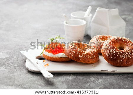 Fresh homemade bagels sandwiches with cream cheese and red caviar on ceramic serving board, selective focus - stock photo