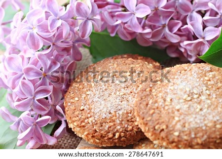 fresh homemade baked cookies for breakfast with flowers on table - stock photo
