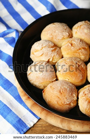 Fresh homemade bread buns from yeast dough on pan, on color napkin background - stock photo