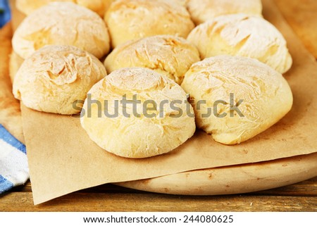 Fresh homemade bread buns from yeast dough on wooden board, on wooden background - stock photo
