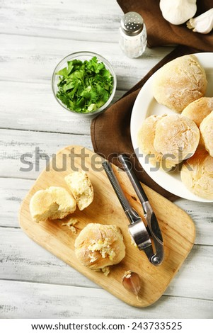 Fresh homemade bread buns from yeast dough on wooden tray, on color wooden background - stock photo