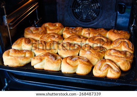 Fresh homemade buns in the oven - stock photo