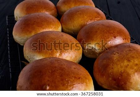 Fresh homemade burger buns on black background - stock photo