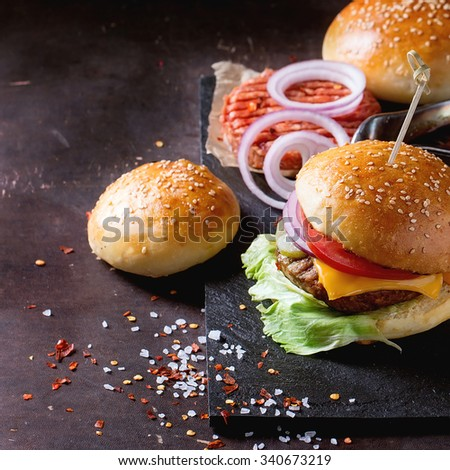 Fresh homemade burger on black slate and raw cutlet and sliced onion, served with sea salt and pepper over dark background. Square image with selective focus - stock photo
