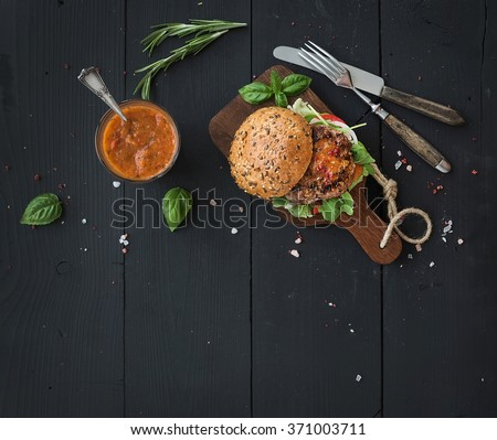 Fresh homemade burger on dark serving board with spicy tomato sauce, sea salt and herbs over dark wooden background. Top view, copy space, horizontal - stock photo