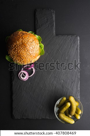 Fresh homemade burger on dark slate stone board, pickles and sliced onion over black background. Top view, copy space