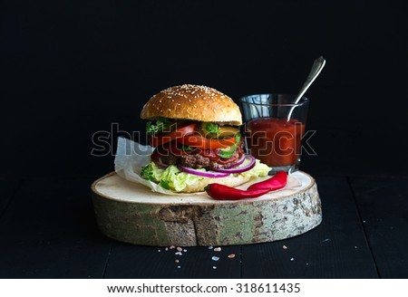 Fresh homemade burger on wooden serving board with spicy tomato sauce, sea salt and herbs over black background - stock photo