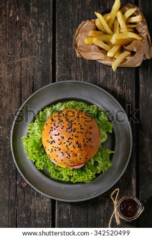 Fresh homemade burger with black sesame seeds in metal plate and fried potatoes in backing paper, served with ketchup sauce in glass jar over old wooden surface. Dark Rustic style. Top view - stock photo