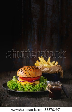 Fresh homemade burger with black sesame seeds in old metal plate with fried potatoes, served with ketchup sauce in glass jar over old wooden table with dark background. Dark rustic style. - stock photo
