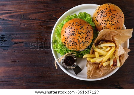 Fresh homemade burger with black sesame seeds in white plate with fried potatoes, served with ketchup sauce in glass jar over dark wooden table. Top view