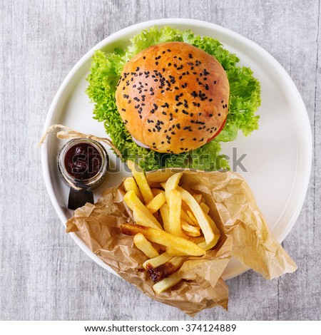 Fresh homemade burger with black sesame seeds in white plate with fried potatoes, served with ketchup sauce in glass jar over gray wooden surface. Flat lay. Square image - stock photo