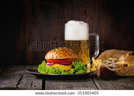 Fresh homemade burger with in old metal plate with fried potatoes in baking paper, served with glass of lager beer and ketchup sauce over old wooden table with dark background. Dark rustic style. - stock photo