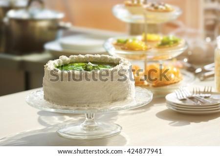 Fresh homemade cake with sliced kiwi on a glass plate. - stock photo