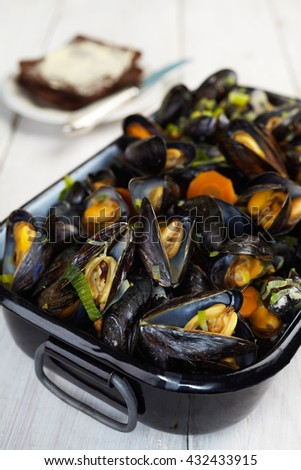 Fresh homemade cooked mussels with carrots and leek, bread and butter
