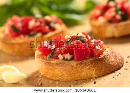 Fresh homemade crispy Italian antipasto called Bruschetta topped with tomato, garlic and basil on wooden board (Selective Focus, Focus on the front of the first bruschetta) - stock photo