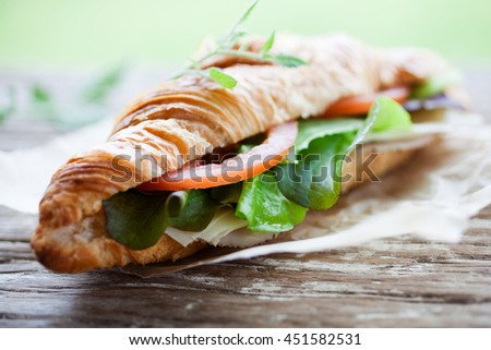 Fresh homemade croissant with ham and salad - stock photo